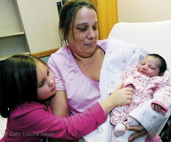 Karleigh Deeanne Evans, Bartow County's first baby of 2010, gets acquainted with her sister, Katlin, and mother, Dee Evans.  Picture by Skip Butler at Daily Tribune